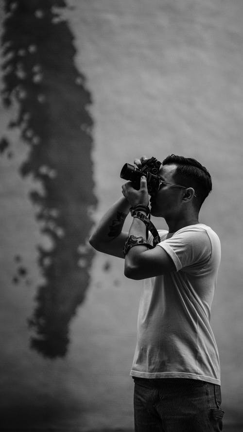 Grayscale Photo of Man Taking Pictures Using a Camera