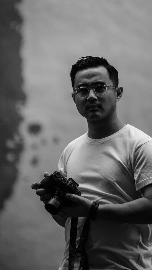 Grayscale Photo of Man Wearing Crew-neck T-shirt Standing While Holding Dslr Camera