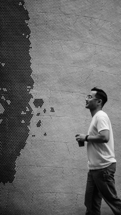 Man in White T-shirt Standing Beside Wall