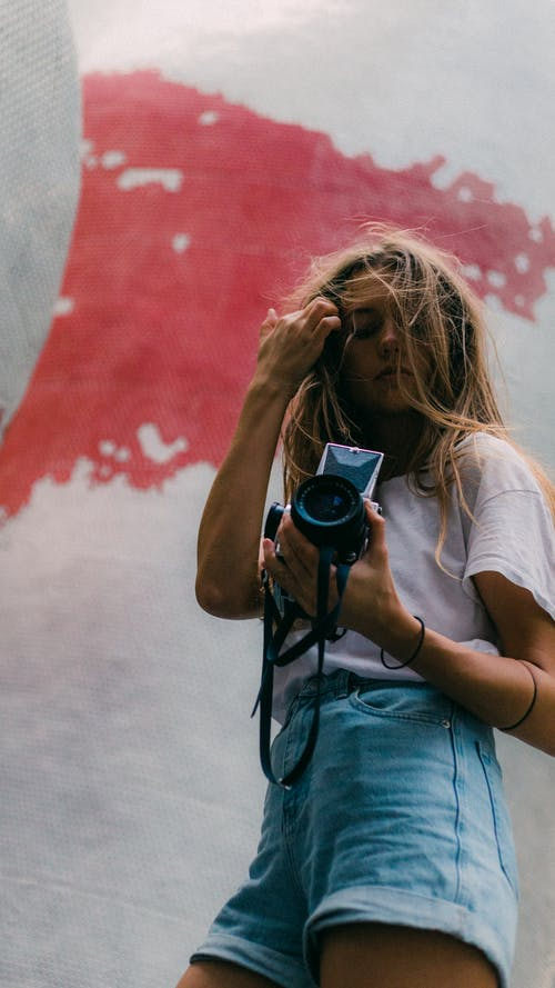 Low-angle Photography of Woman Carrying a Dslr Camera