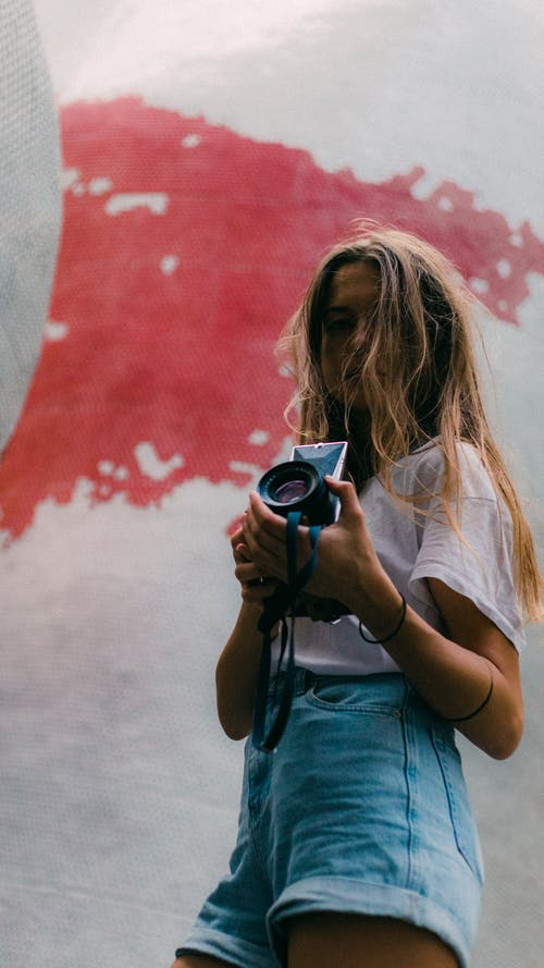 Woman in White T-shirt Holding Dslr Camera