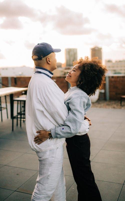 Man Wearing White Jacket and Woman Wearing Blue Jacket Hugging