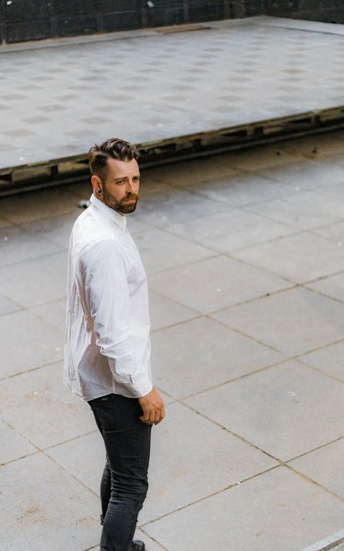 Man in White Dress Shirt Standing on Pavement