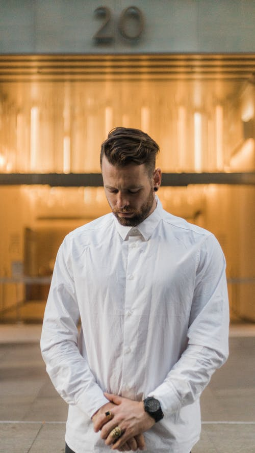 Selective Focus Photo of Man in White Dress Shirt Posing While Looking Down