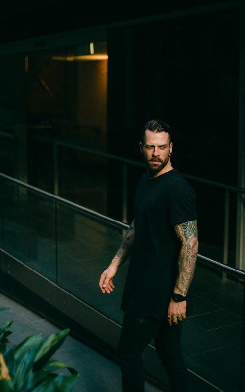 Man in Black T-shirt Standing Beside Glass Rail