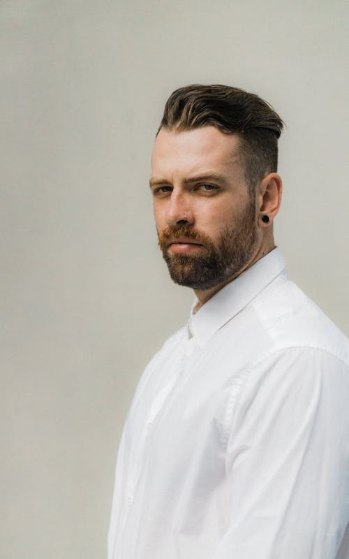 Man Wearing White Dress Shirt With Piercing Look With His Eyes