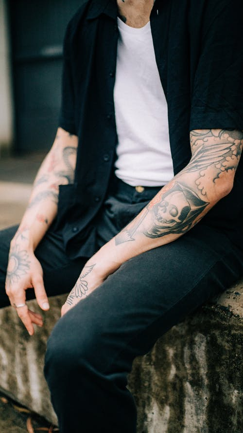 Man in Black Dress Shirt  With Arm Tattoos Sitting On A Concrete Bench
