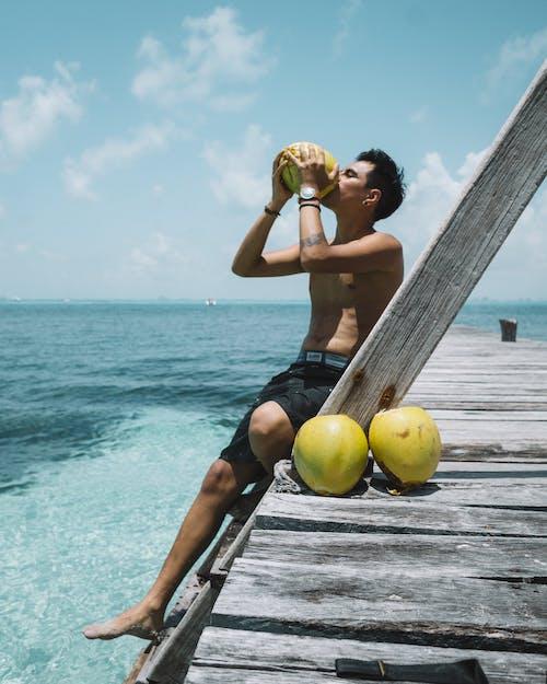 ココナッツを飲む男