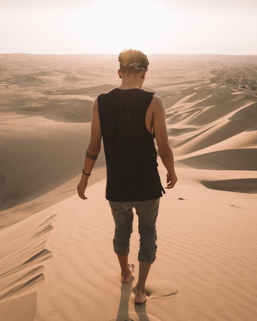 Back view Photo of Man Walking on Sand in the Desert