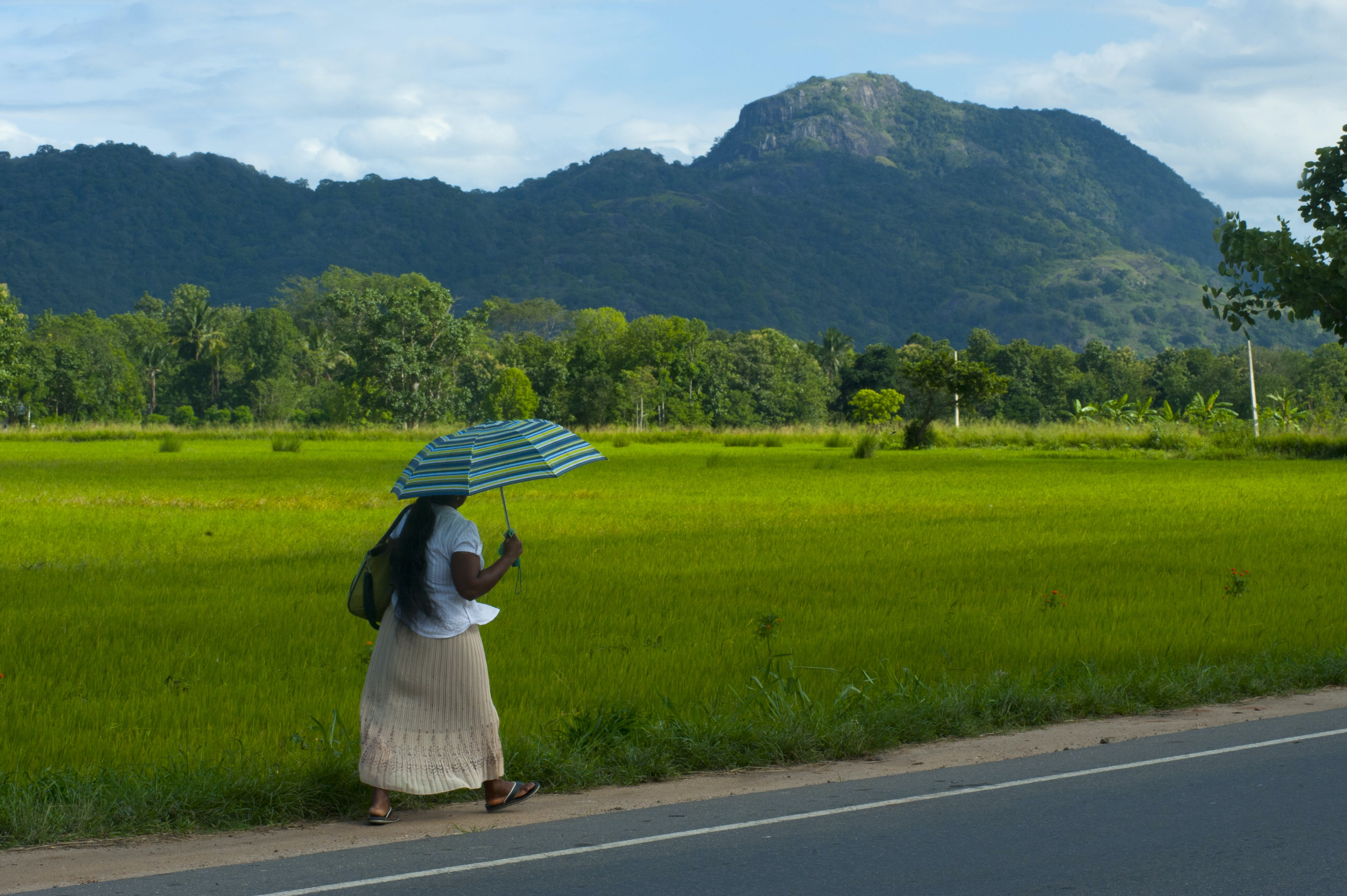 Woman in White Skirt Walking Along Road Holding Teal Umbrella