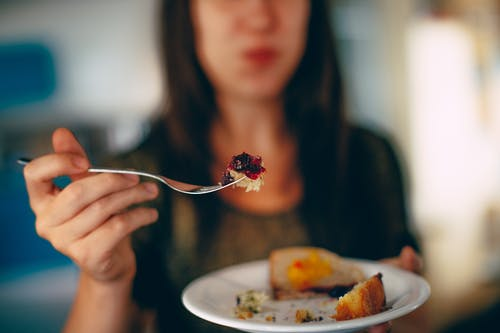 Crop woman eating delicious pie in plate