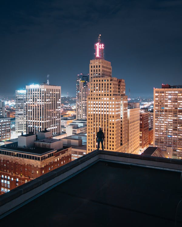 Person Standing at the edge of Building at Night