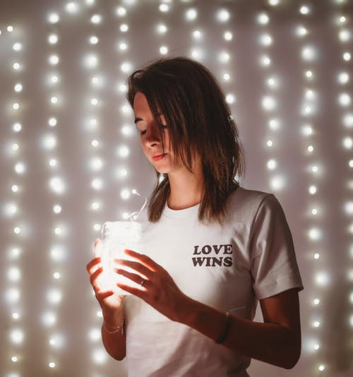 Woman Wearing White Crew-neck Shirt Holding Lamp