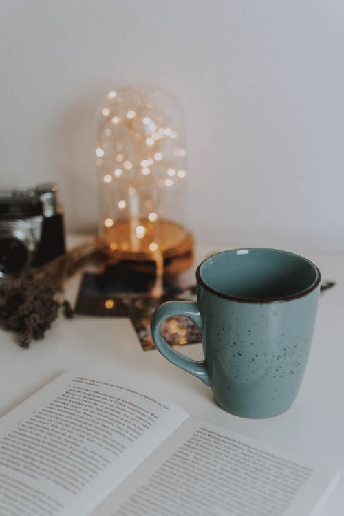 Green Mug Beside A Book