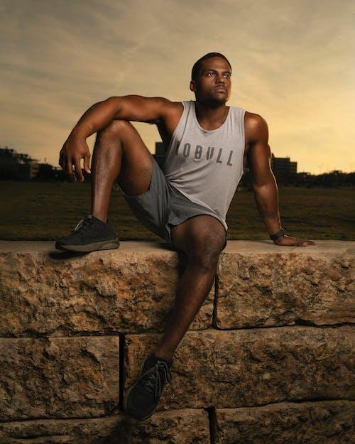 Photo of Man Sitting on Concrete Blocks