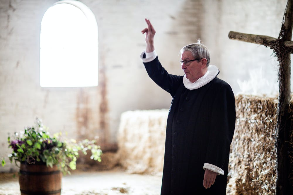 Priest raising his right arm. | Photo: Pexels