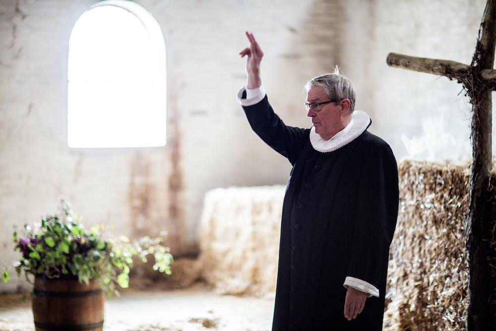 A priest raises his right arm. | Photo: Pexels