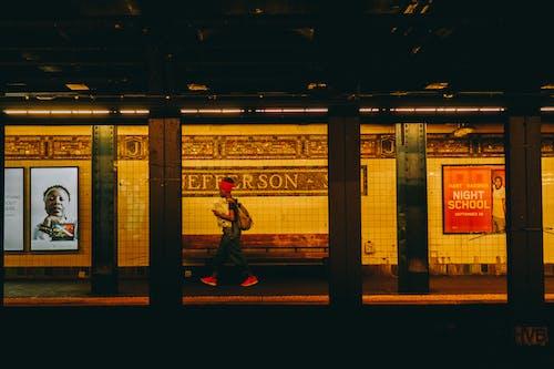 Person, Die Schwarzes Oberteil Und Rotes Kopftuch Trägt, Die Auf U Bahn Gehen