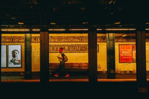Person Wearing Black Top and Red Bandana Walking on Subway