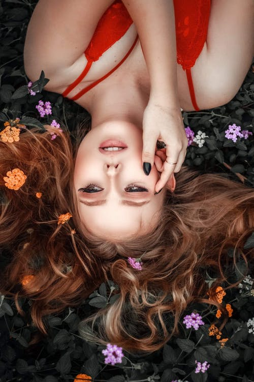 Top view of young alluring female with makeup in lace red top lying upside down on ground with colorful flowers in curly hair