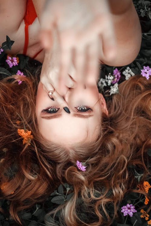 Woman Lying Down on Flowers and Leaves