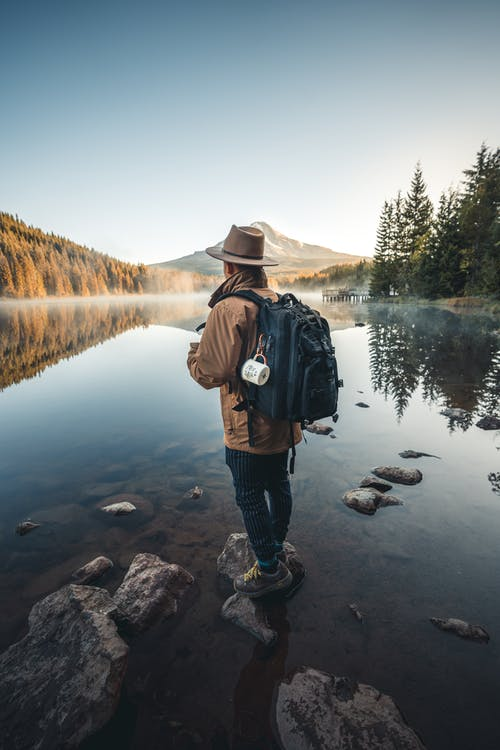 Man in Brown Jacket and Brown Hat Standing on Rock Near Lake
