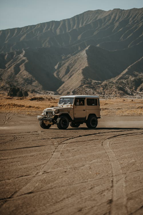 White and Black Jeep Wrangler on Dirt Road