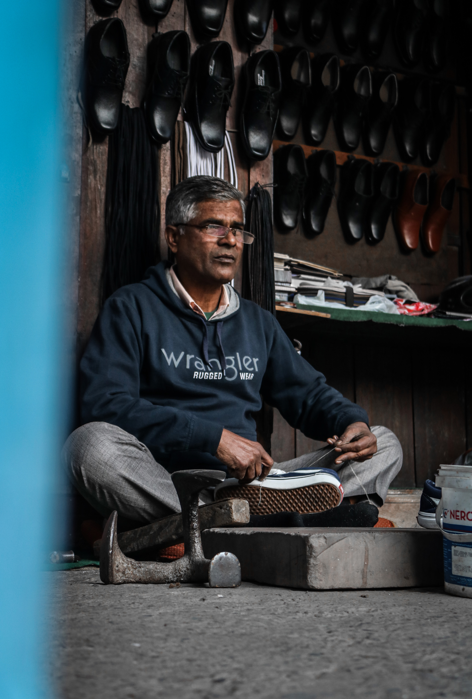 Elderly Man In His Shop Repairing Shoes