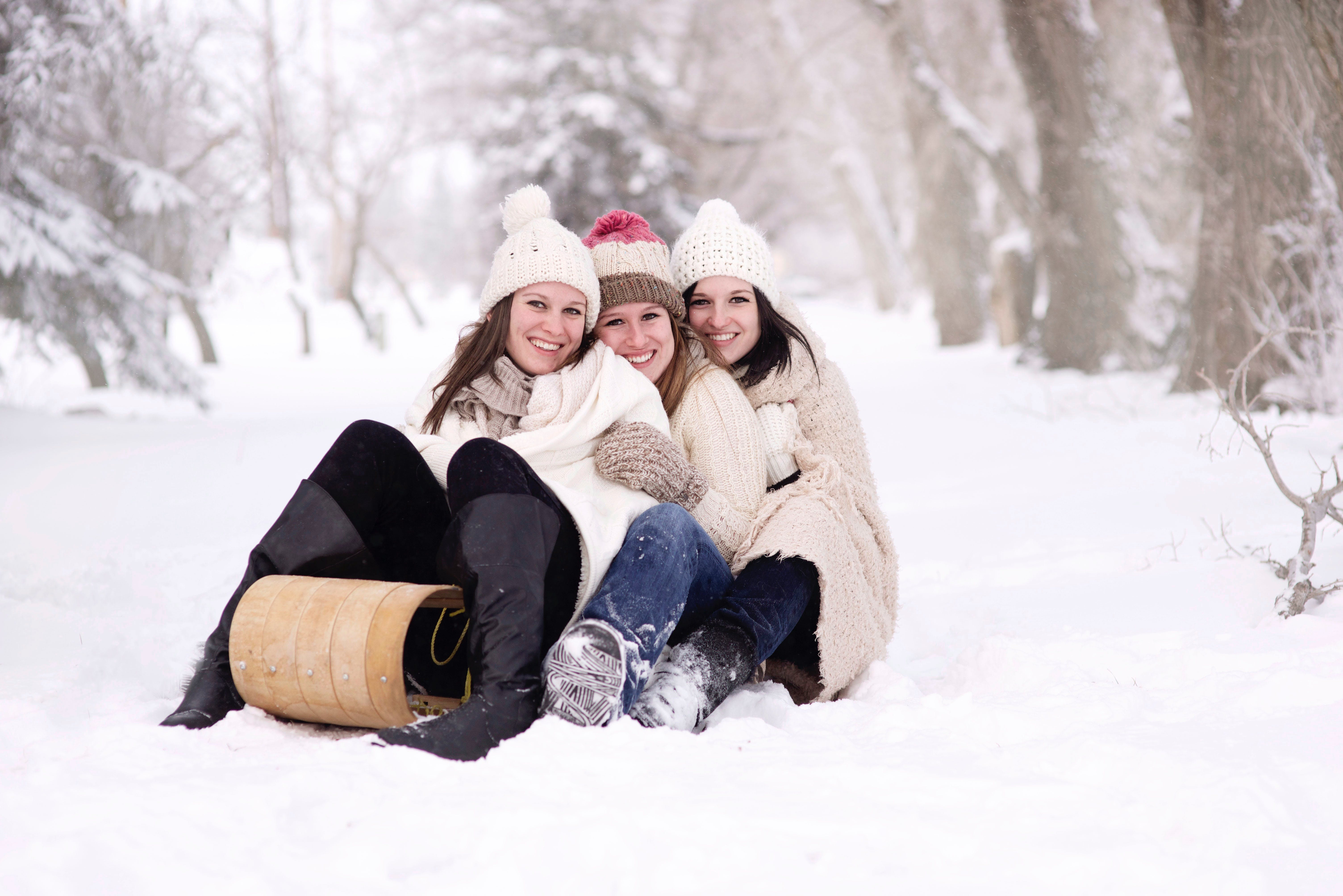 Three Women Sitting on Snow Covered Ground during Day