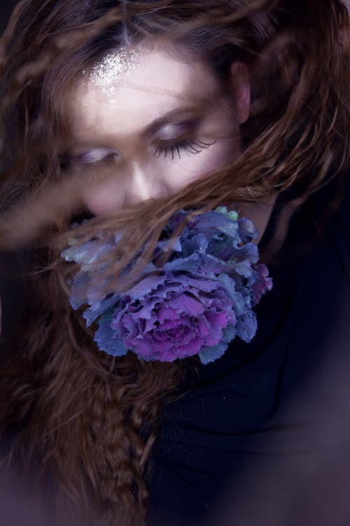 Concept Photography Of A Woman With Extra Long Lashes With A Blue Flower Covering Her Mouth