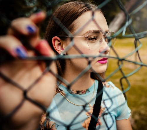 Photo Of Woman Holding Chain Link Fence