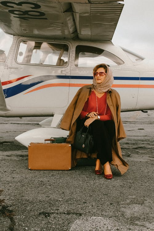 Photo of Woman Sitting Near Airplane