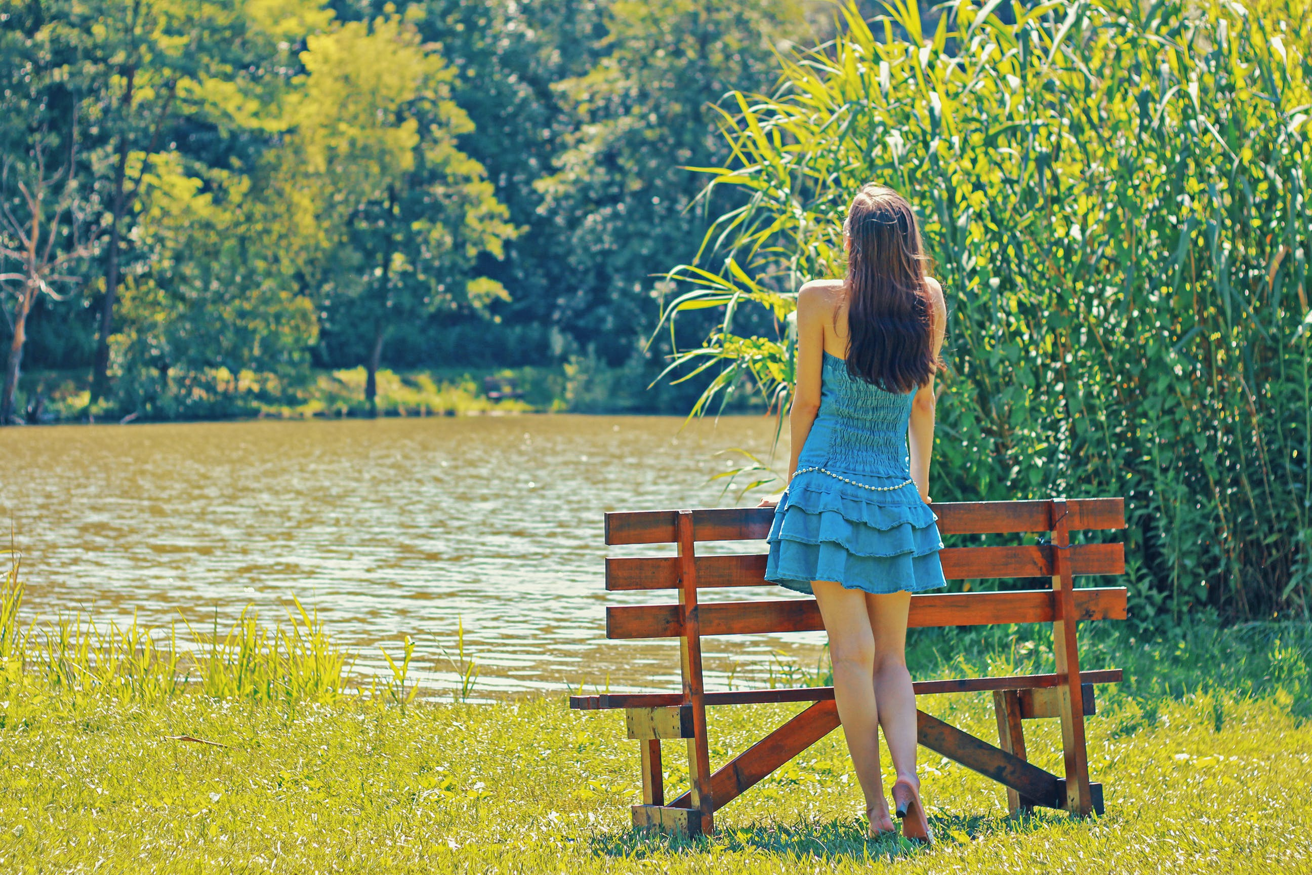 Full Length Rear View of a Woman Overlooking Calm Lake