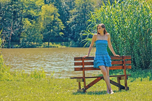 Woman Standing Behind Bench