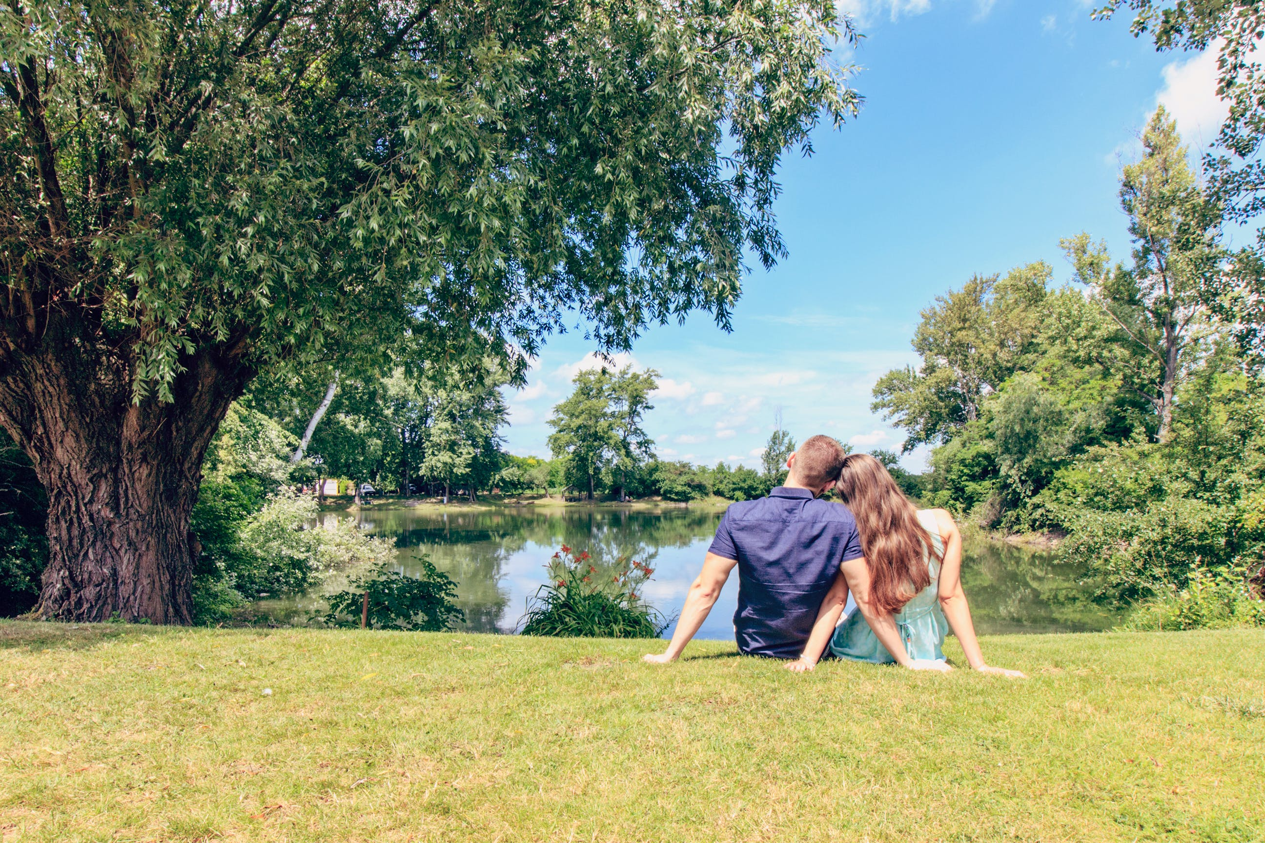 Couple Sitting on Grass Field in Front of Body of Water