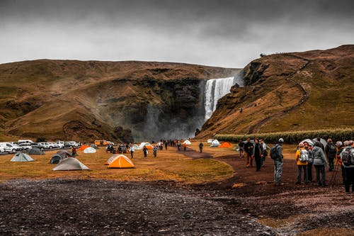 People Standing on Camping Site Near Waterfalls