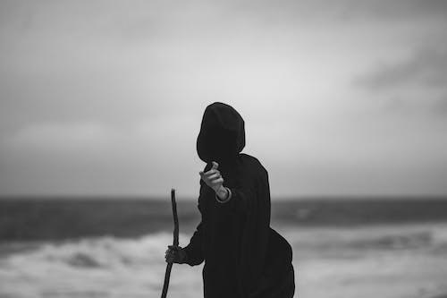 Man in Black Hoodie Holding Stick