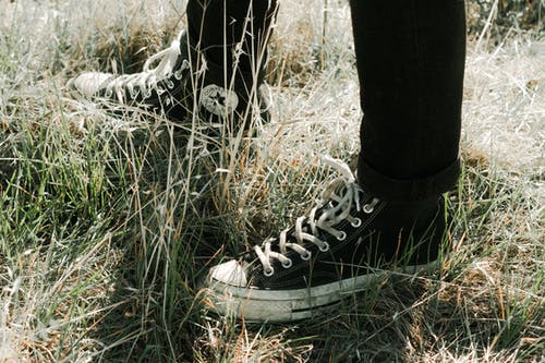 Unrecognizable person in sneakers standing on grass