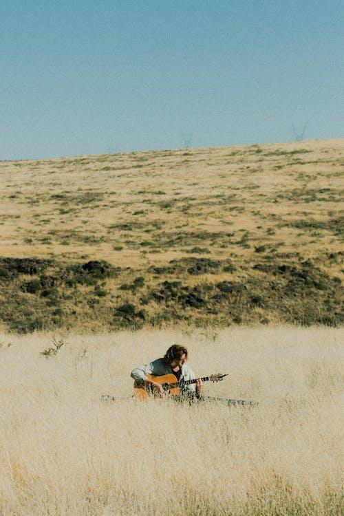 Man Sitting on Grass Field Playing Guitar