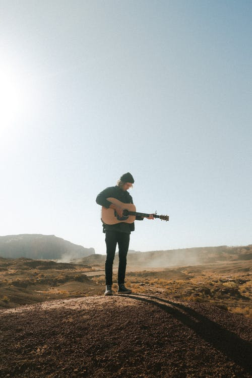 Full body male in warm clothes standing in endless field in morning sunlight and playing guitar under blue sky