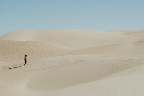 Photo Of Person Walking On Desert