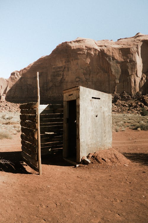 A Small Concrete Structure With A Wooden Fence Built Close To A Rock Mountain In The Desert