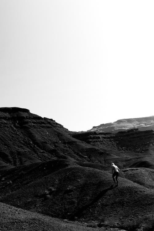 Back view of black and white anonymous traveler walking on rough hill towards mountain in wild valley