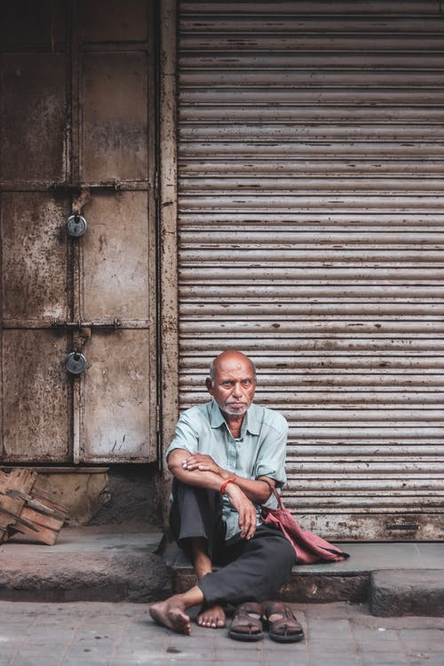 Photo Of Old Man Sitting On Sidewalk