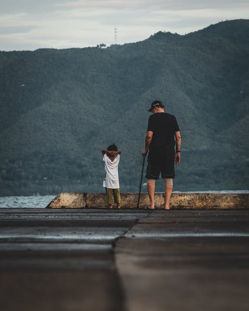 Man and Child Near Body of Water