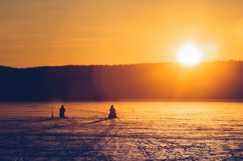 Silhouette Of Two Persons Sitting While Snow Fishing On An Iced Covered Body Of Water At Dawn