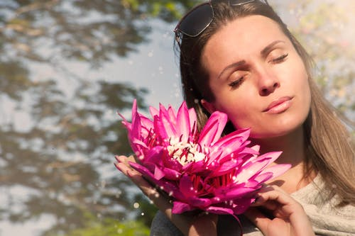 Woman Holding Pink Water Lily Flowers