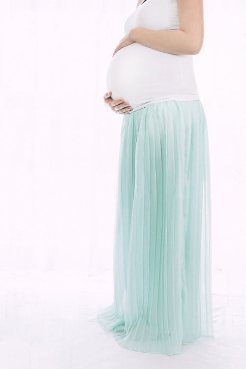 Pregnant Woman Standing in Front of White Wall