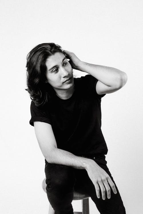 Foto d'estoc gratuïta de assegut, blanc i negre, cabells llargs, camisa negra