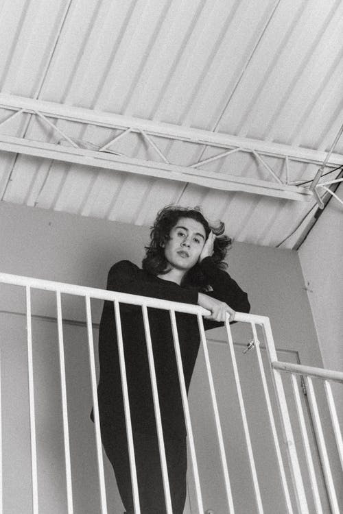 Monochrome Photo Of Man Leaning On Handrail